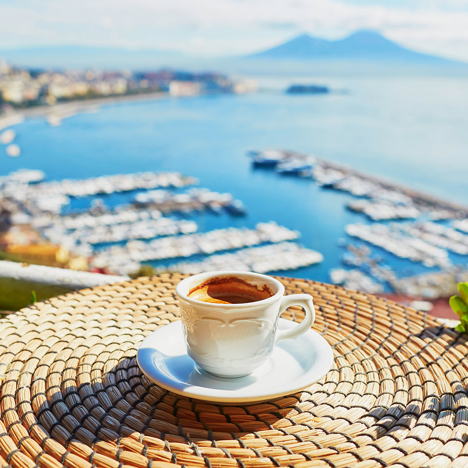 A cup of espresso coffee on a table in front of a view of Vesuvius mount in Naples, Campania, Southern Italy