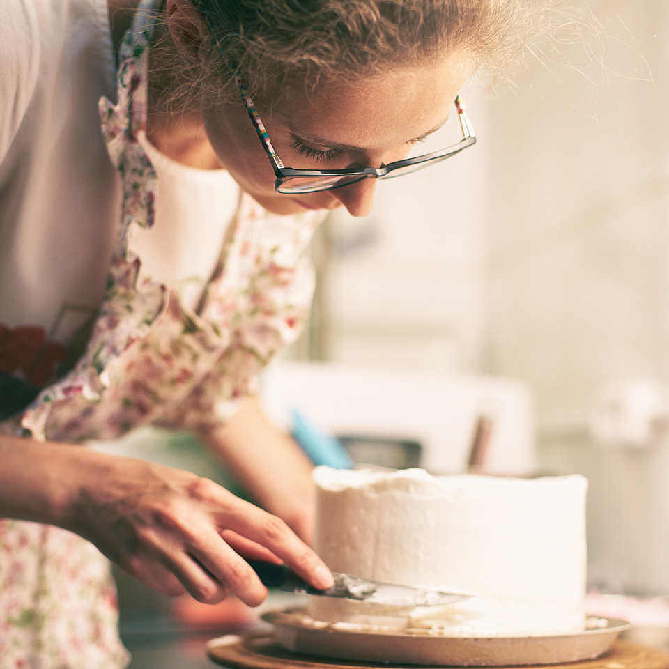 Woman wearing an apron, decorating a cake