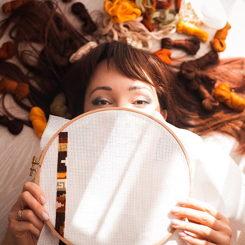 Woman lying on the floor with fabric in her hair, holding a cross-stitching hoop in front of her face