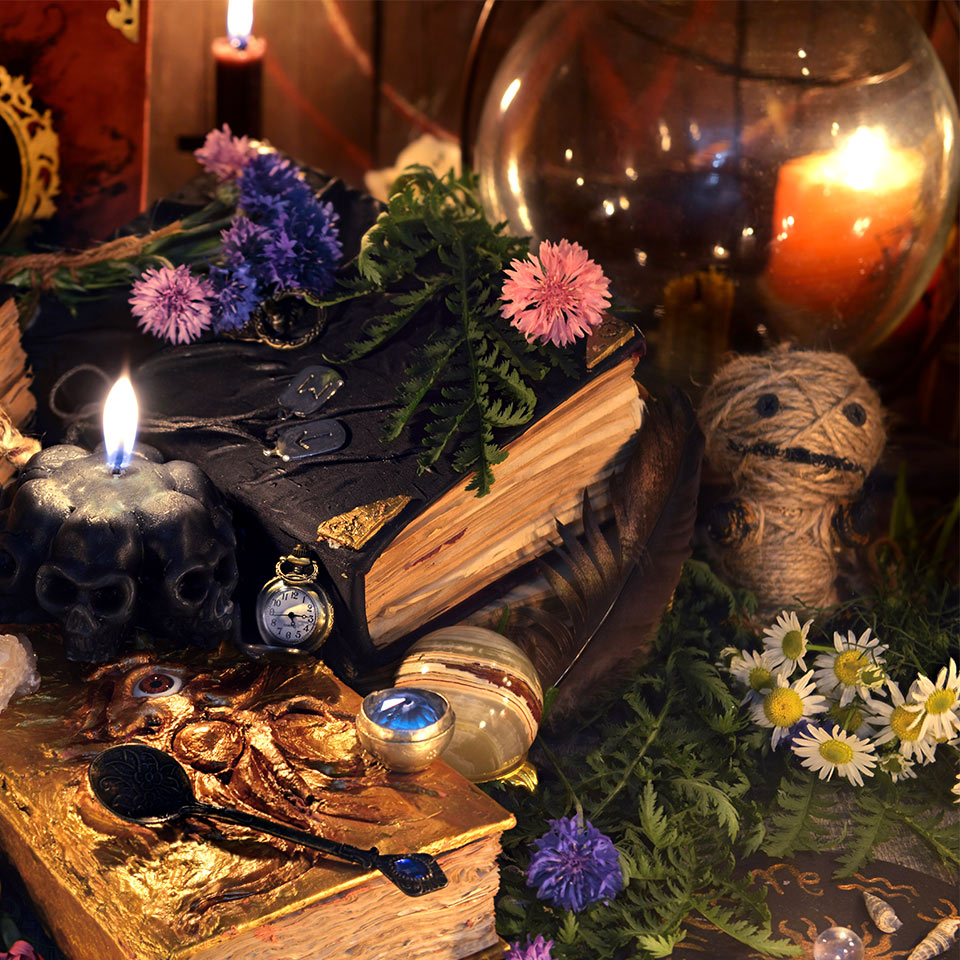 Various hoodoo objects on a table including a book, a doll, candles, and flowers
