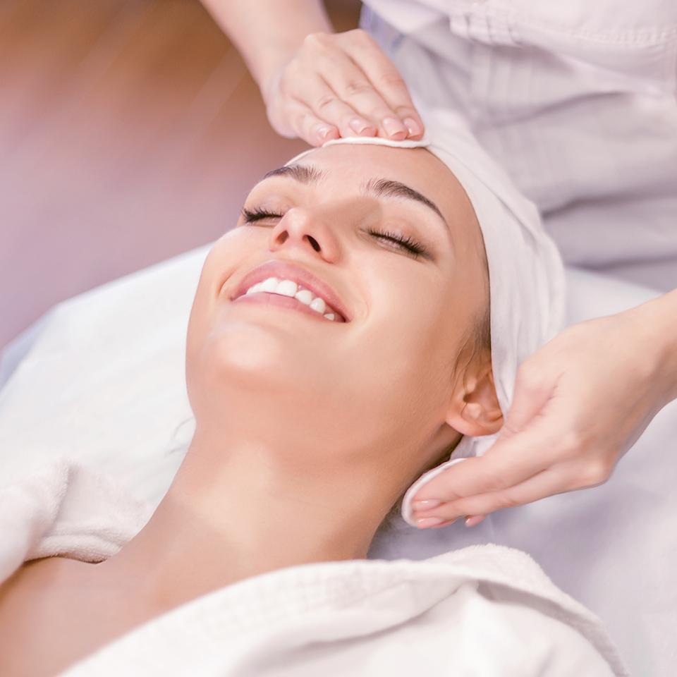 Smiling woman receiving a holistic facial