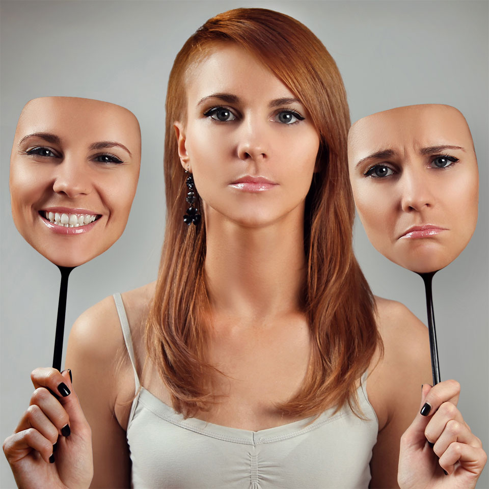 Young expressionless woman with holding up two faces - one with happy expression, one with a unhappy expression
