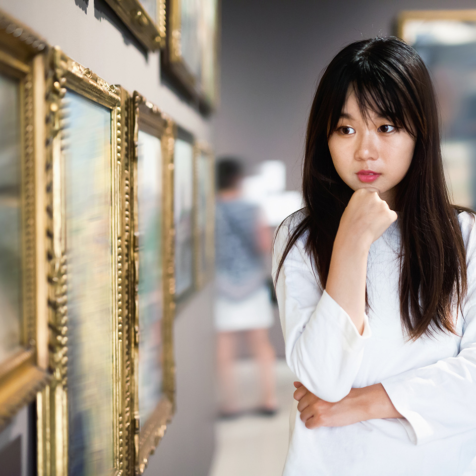 Woman in an art gallery viewing paintings