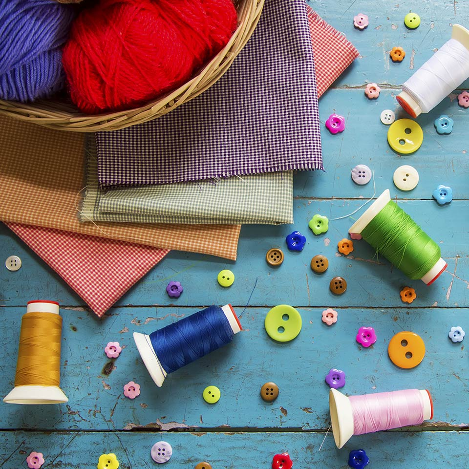 Cotton reels, wool, buttons, and fabrics strewn across a blue tabletop