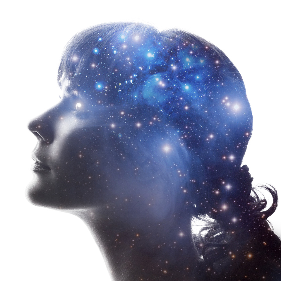 A double exposure of the profile of a woman and the cosmos
