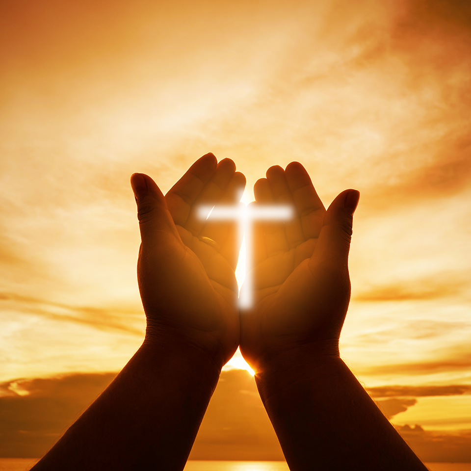 Hands open palm up in worship in front of a rising sun. The sign of the cross is glowing on the hands