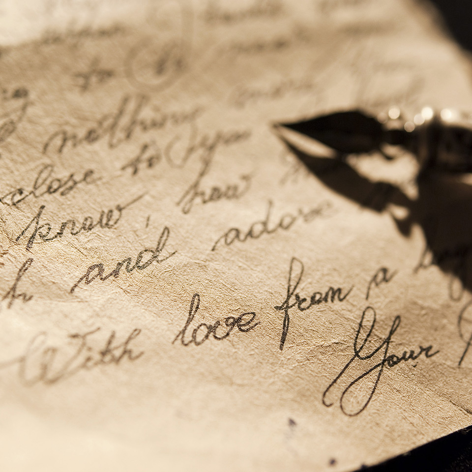 Letter and antique quill on a black background