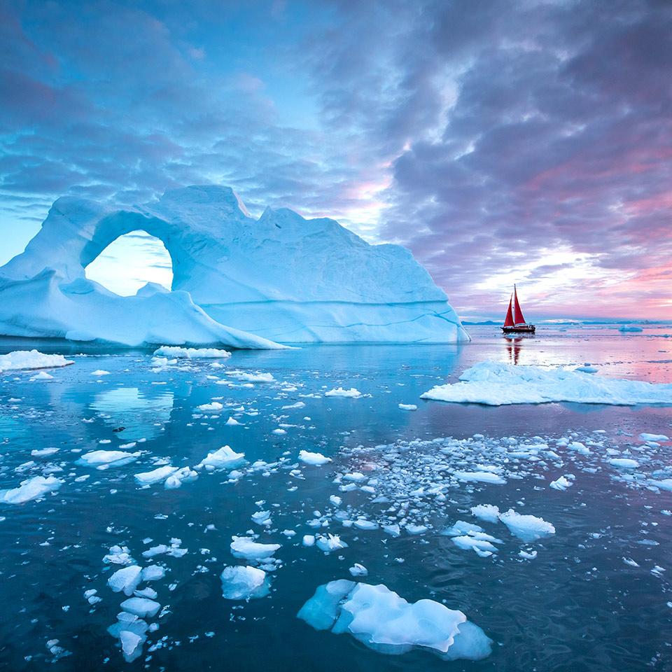 Sailboat cruising among floating icebergs in Disko Bay glacier during midnight sun season of polar summer. Ilulissat, Greenland.