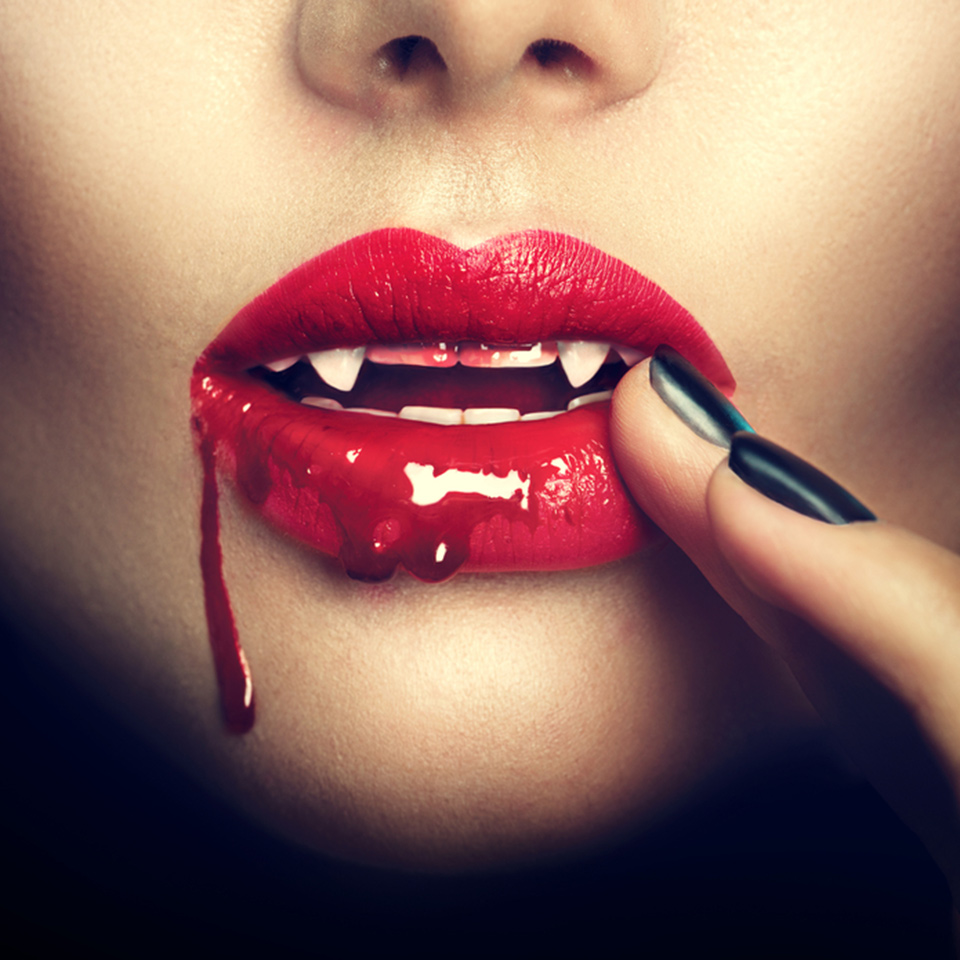 Lips of a female vampire with blood dripping from the corner of her mouth