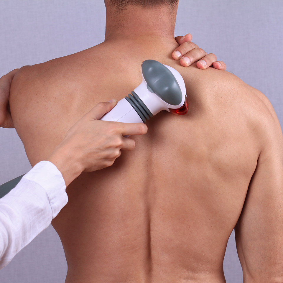 Therapist applying an infrared treatment on a man's back