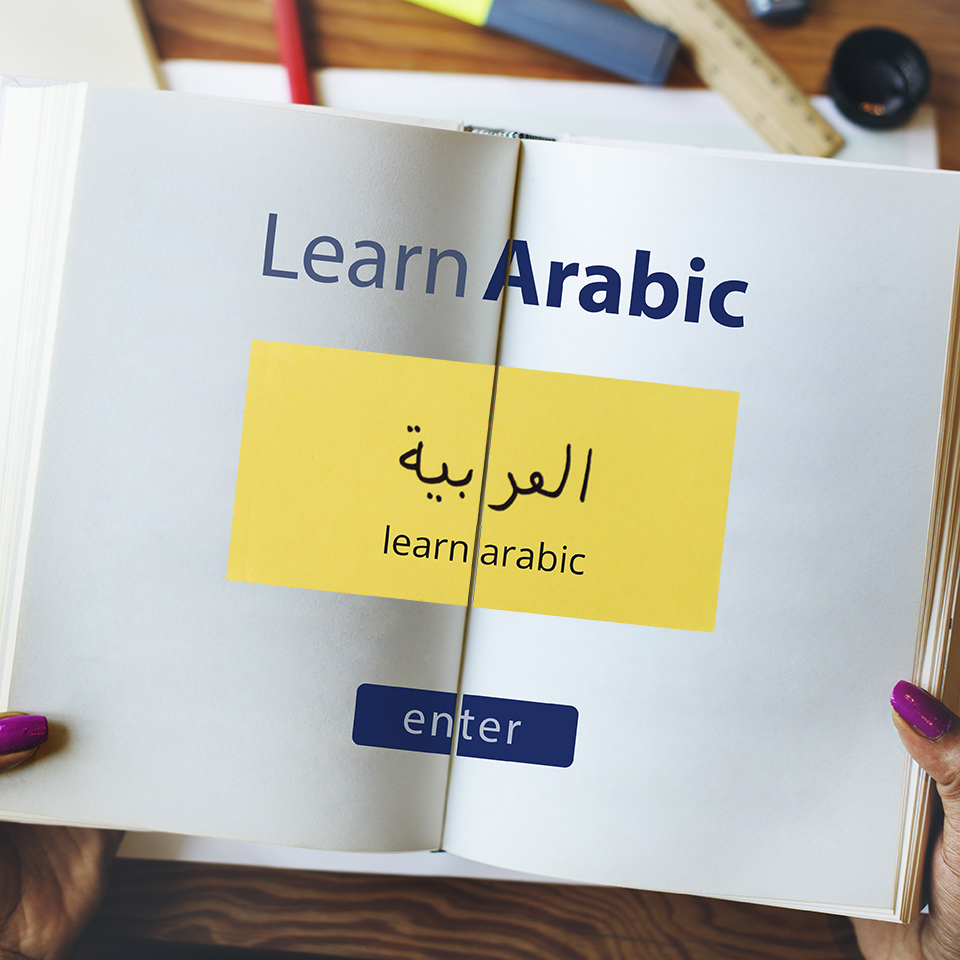 An open book with the words 'Learn Arabic' written across it in English and Arabic