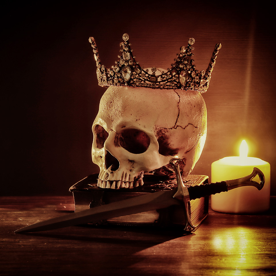 Human skull, old book, sword, crown and burning candle on an old wooden table and dark background