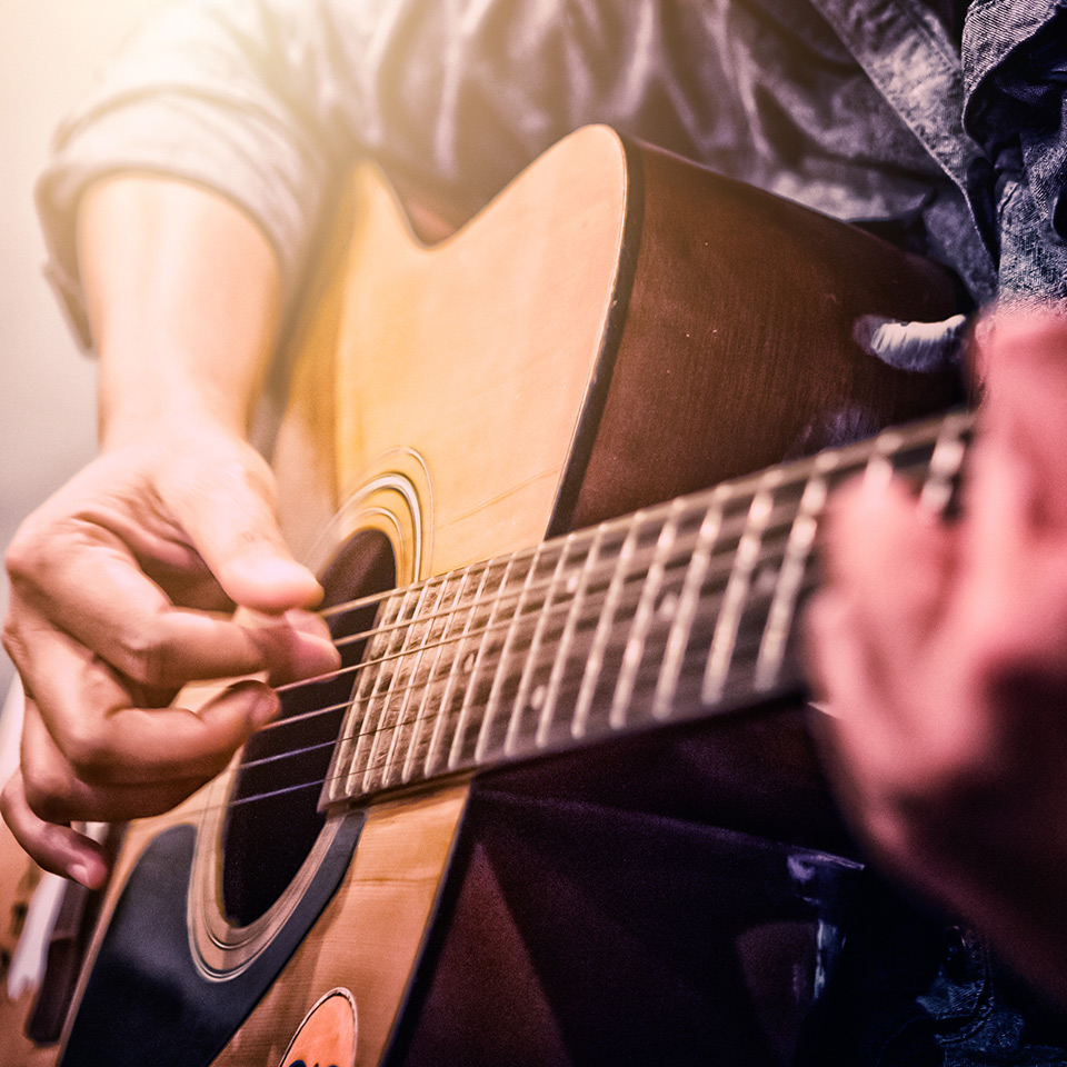 Close up of hands playing an acoustic guitar