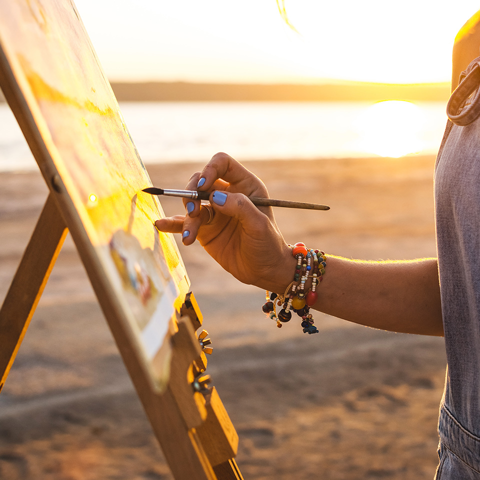 Artist painting a landscape in the open air on the beach