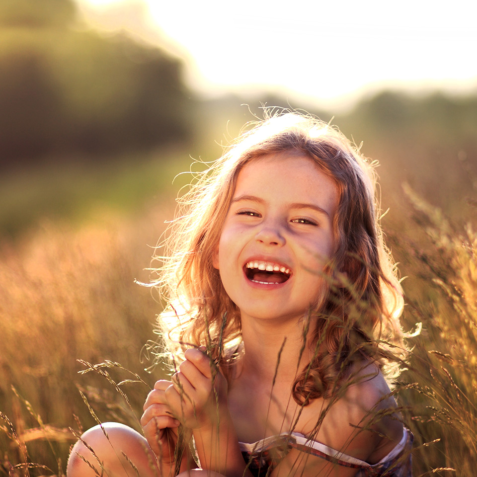 Young girl laughing in a meadow