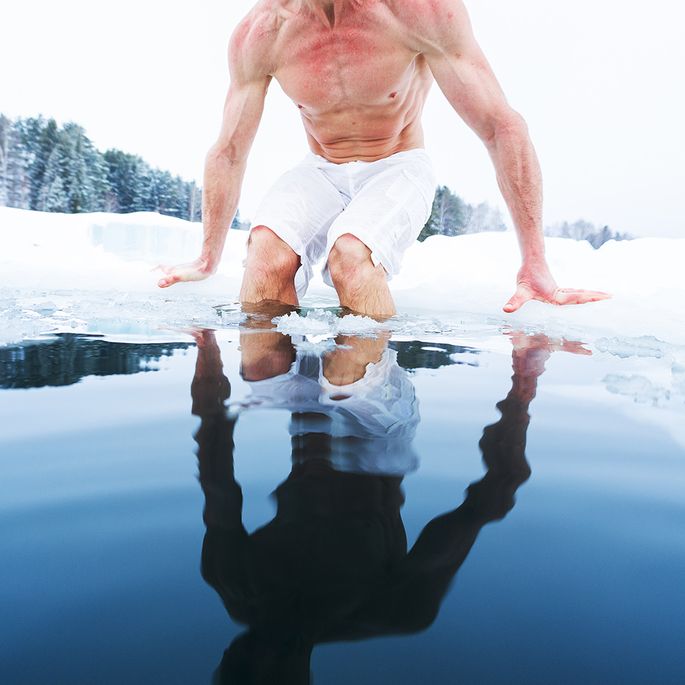 A man lowering himself into ice cold water