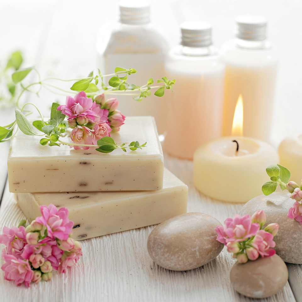 Aromatherapy products laid out on a wooden table. These include soap, candles, and lotions. Flowers and smoothed pebbles are also visible in the image.