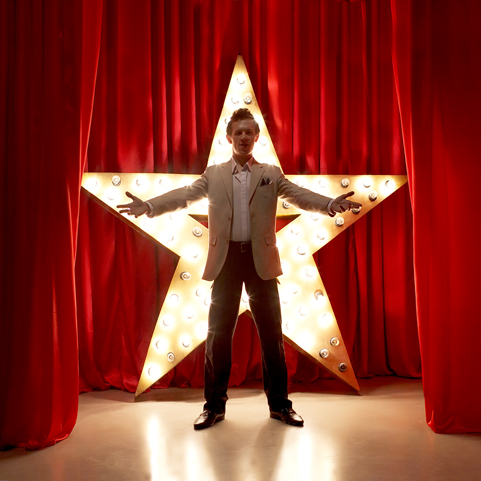 Man on stage with a star in background