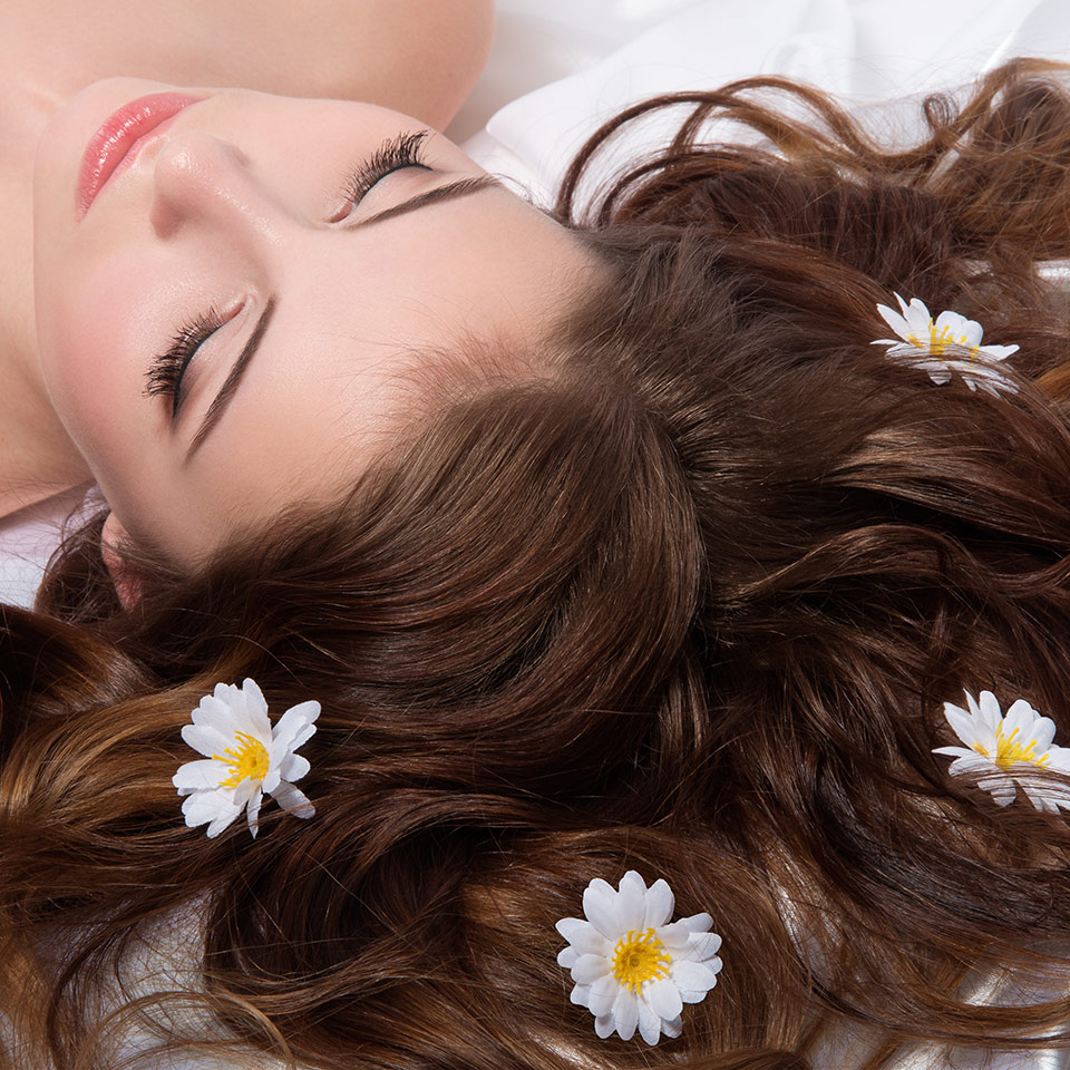 Portrait of woman with camomile flowers in her hair