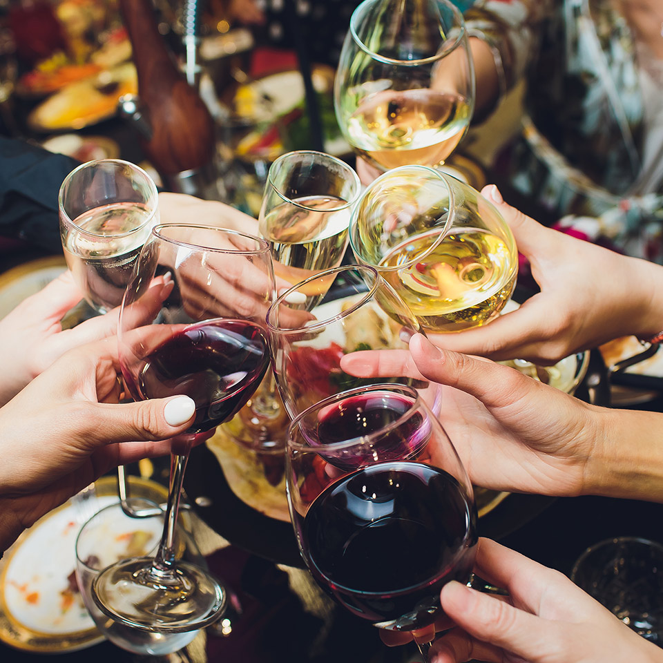Wine glasses in the hands of people at a party