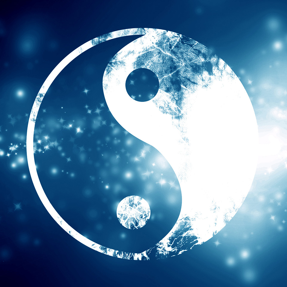 Yin yang symbol in white on a blue background with sparkling stars