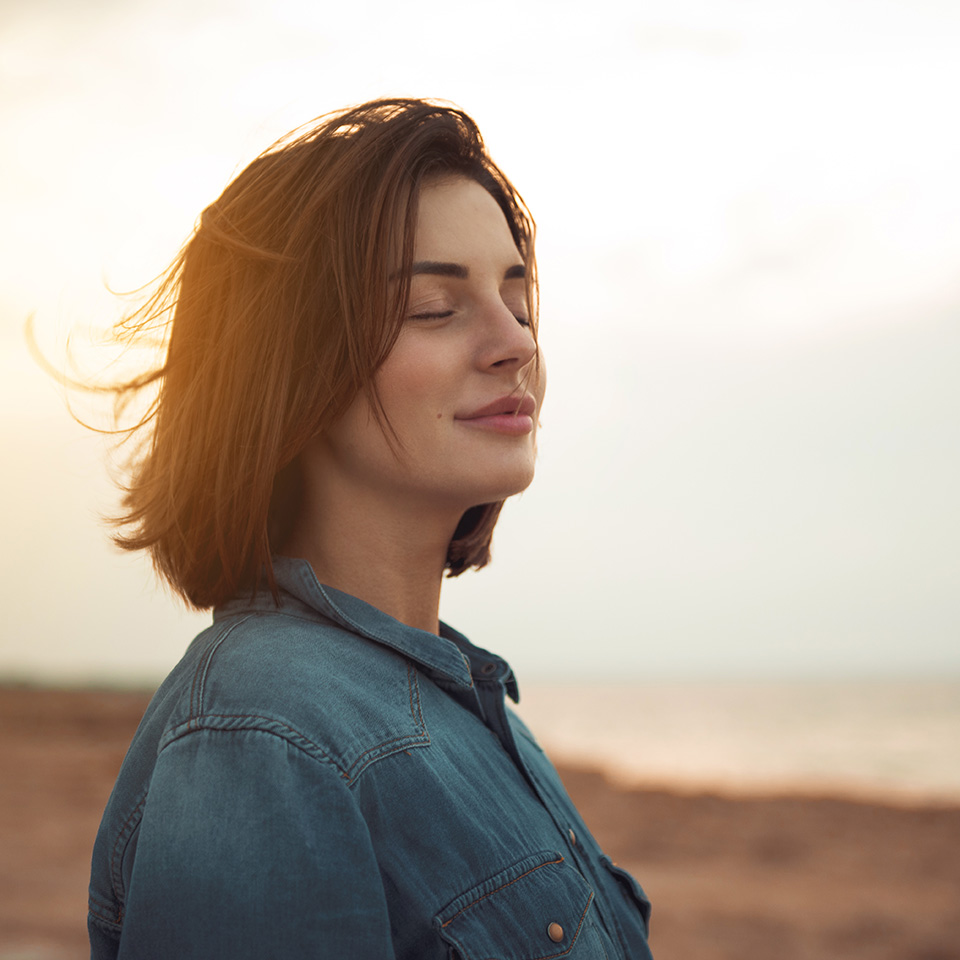 Young woman standing near the sea with closed eyes and calm, serene expression on her face.