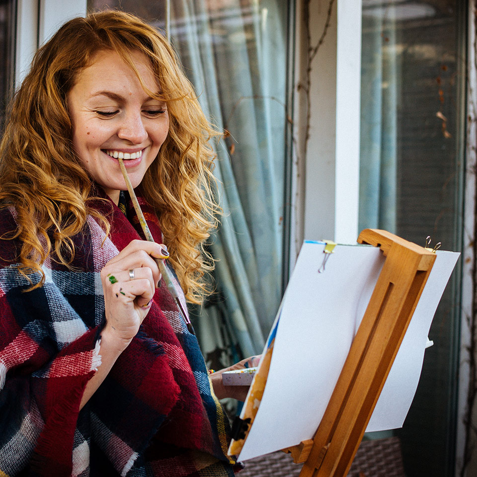 Artists smiling and painting with watercolour at an easel