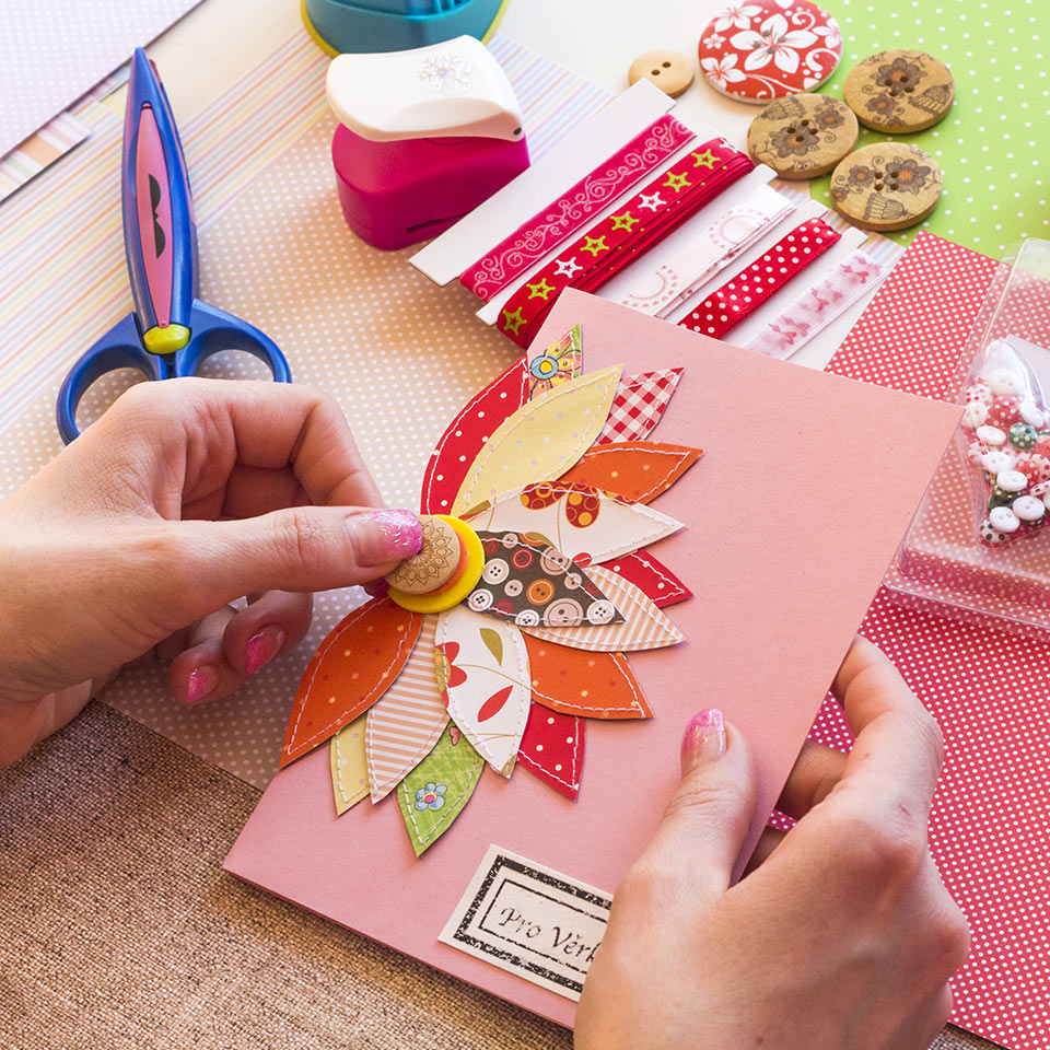 Hands making a handmade card with a fabric and button flower on it