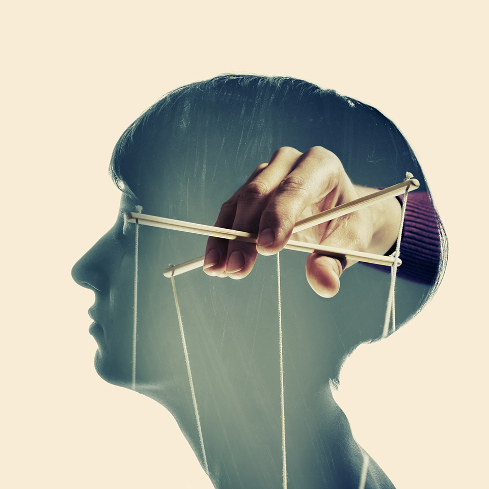 Double exposure of a head with hand inside holding puppeteer controller strings