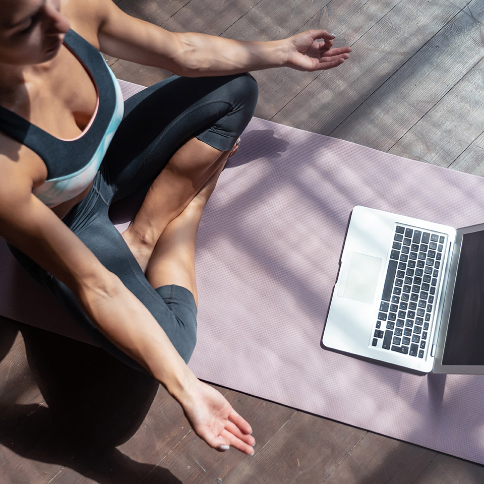 Top view of a woman learning to be a yoga teacher by following lessons on a laptop