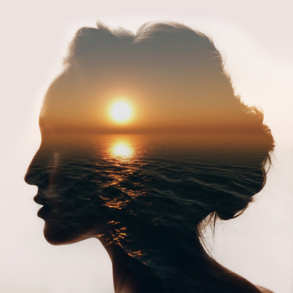 Silhouette of a woman's head, the silhouette is filled with an image of a sunset over an ocean